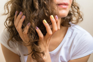 Female hands with a bright purple and yellow manicure holding brown curly hair.