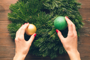 Female hands with a red manicure holding Christmas decorations. View from above.