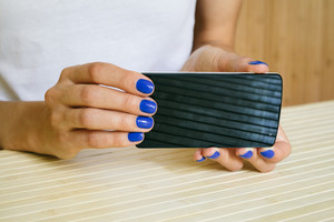 Female hands with blue manicure holding smartphone
