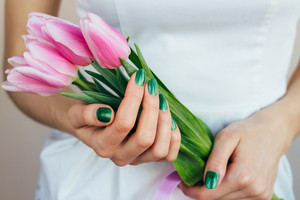 Female hands with green manicure holding pink tulips, close-up