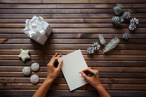 Female hands with pen over piece of paper with spice-cakes, decorative silver cones, giftbox and white toy star near by