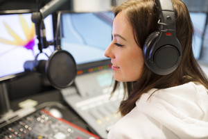 Female Host Wearing Headphones At Radio Studio