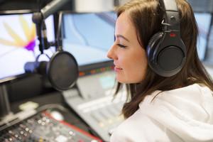 Female Host Wearing Headphones At Radio Studio