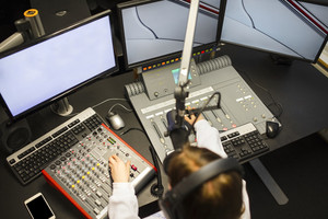 Female Jockey Using Music Mixers And Screens In Radio Studio