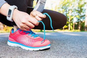 Female jogger ties her running shoes in preparation for a jog