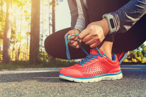 Female jogger tying her shoes preparing for a run outside