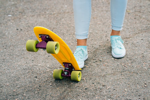 Female legs in jeans and sneakers standing near bright yellow skateboard