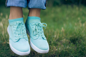 Female legs in jeans and sport shoe floating in the air above the green grass in the park. Flying sneakers outdoors. Conceptual image.