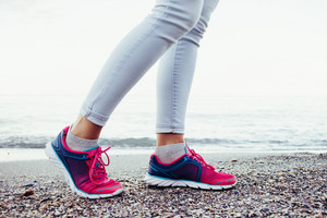 Female legs in pink and blue sneakers and jeans are on the beach