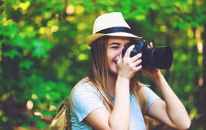 Female photographer in the forest with a camera