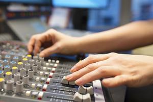 Female Radio Host Using Music Mixer In Studio