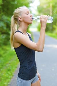 Female runner drinking water after running