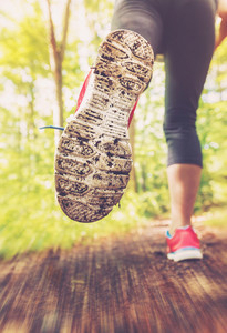 Female runner jogging outdoors through a forest trail