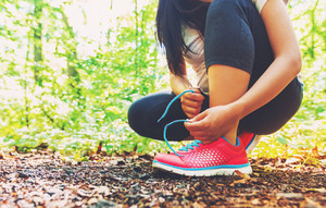 Female runner lacing her sneakers on a forest trail