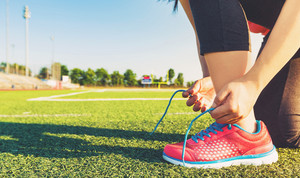Female runner lacing her sneakers on a stadium field