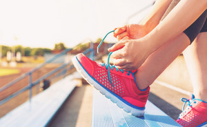 Female runner lacing her sneakers on in the bleachers of a stadium