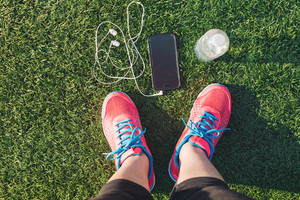 Female runner looking down at her feet, phone and water bottle in a field