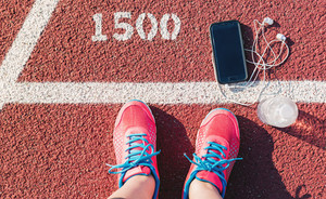 Female runner looking down at her feet, phone and water bottle on a running track