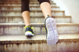 Female runner running up the stairs in city center, closeup on shoes