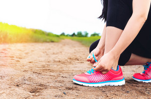 Female runner tying her running shoes on a sandy trail