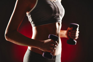 Female torso in activewear during exercise with dumbbells