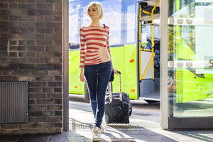 Female traveler going off the bus at terminal