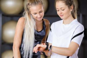 Female Workout Friends Using Pedometer In Gym