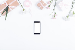 Festive composition: mobile phone, boxes with gifts, ribbons and flowers lie on a white table, top view