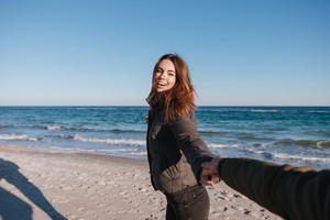 First person view of man holding hand of happy woman in warm jacket on beach