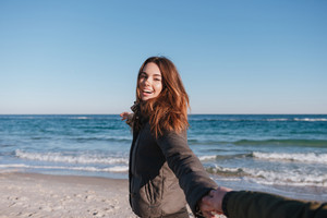 First person view of man holding hand of smiling woman in warm jacket on the beach