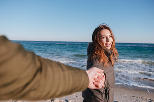 First person view of man holding hand of woman in warm jacket on beach near the sea