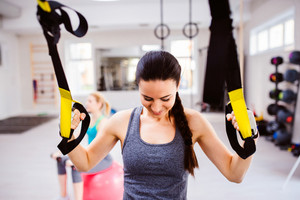 Fit attractive woman in gym training arms with trx fitness strips