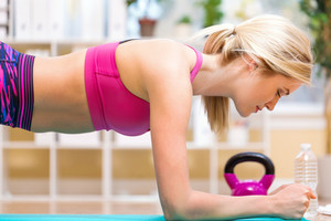 Fit healthy young woman doing a plank indoors