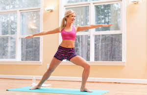 Fit healthy young woman doing stretches indoors