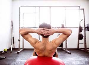 Fit hispanic man at abdominal crunch muscles exercises on fitness ball during training in fitness gym. Rear view.