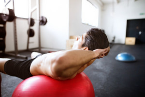Fit hispanic man at abdominal crunch muscles exercises on red fitness ball during training in fitness gym.