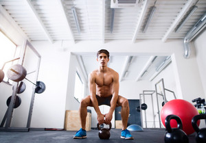 Fit hispanic man doing strength training, doing kettlebell swings in crossfit gym