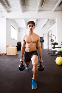 Fit hispanic man doing strength training, doing lunges with kettlebells in crossfit gym