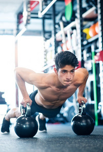 Fit hispanic man doing strength training, doing push ups on kettlebells in modern gym