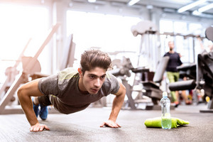 Fit hispanic man in gym training, doing push ups