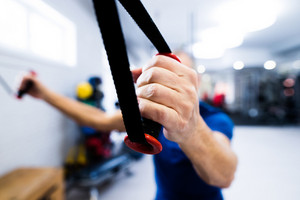 Fit senior man in sports clothing in gym working out with resistance bands. Close up of his arm.
