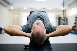 Fit senior man lying on a bench in gym in sports clothing working his abs, doing abdominal crunches.