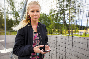 Fit Woman Holding Mobile Phone While Listening Music By Fence