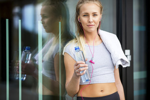 Fit Woman With Water Bottle Leaning Against Glass Wall