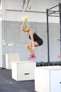 Fit young woman box jumping at the fitness gym