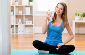 Fit young woman with water bottle ready for yoga at home