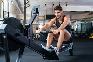 Fitness man doing exercise in gym. looking away