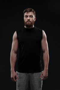 Fitness man in studio. looking at camera. isolated dark background