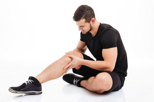 Fitness man injured. in studio. knee injury. isolated white background