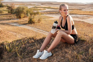 Fitness young woman resting and holding water bottle after jogging outdoors